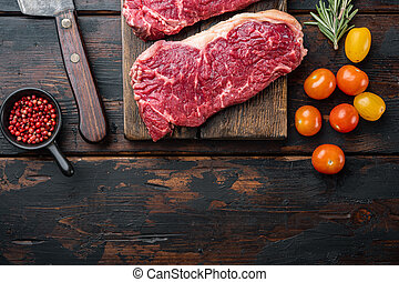 Raw ambassador beef steak, on dark wooden background, top view, with copy space for text