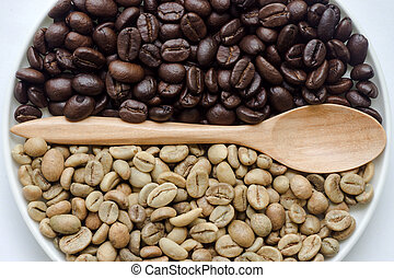 Raw and roasted coffee beans with wooden spoon.