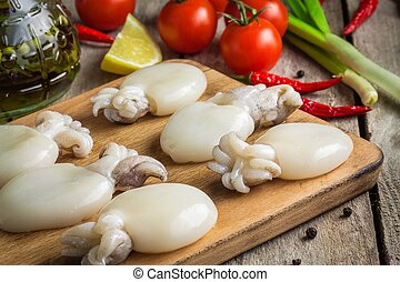 Raw babies cuttlefish on a cutting board with tomatoes, ...