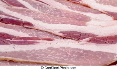 Raw Bacon Strips Rotating - Uncooked bacon strips turning...