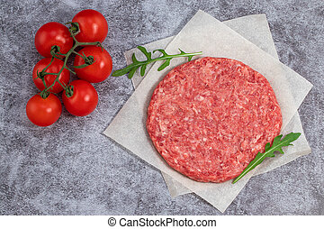 Raw beef burger cutlets with herbs and spices on a concrete background