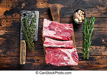 Raw beef calf short ribs meat on a butcher cutting board with cleaver. Dark wooden background. Top view