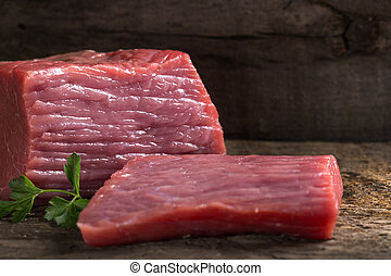 Raw beef meat fillet with parsley on cutting board
