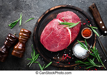 Raw beef meat. Fresh cut of beef meat on board with spices