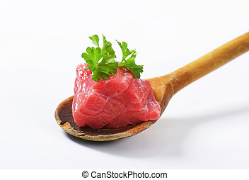 Raw beef meat on wooden spoon