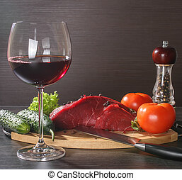 Raw beef meat with vegetables and wine on wooden table