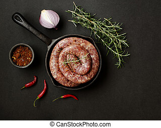 raw beef sausages on a cast-iron pan,  selective focus