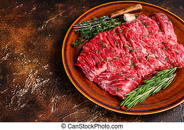 Raw beef skirt meat steak on a rustic plate with herbs. Dark background. Top view. Copy space