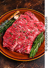 Raw beef skirt meat steak on a rustic plate with herbs. Dark background. Top view