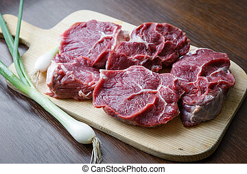 Raw beef slices on a cutting board with a spring onion