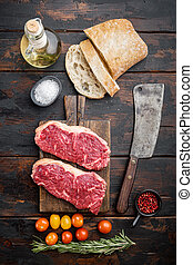 Raw beef steak burger ingredients with marbled meat, on old wooden table, top view