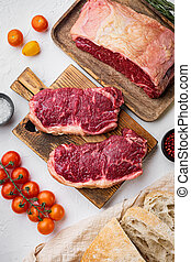 Raw beef steak burger ingredients with marbled meat, on white background, top view