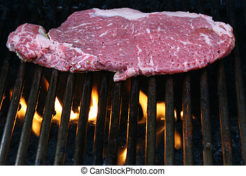 Raw beef steak on a hot grill