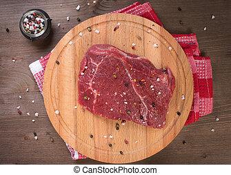 Raw beef steak on board