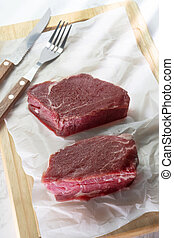Raw beef steak on cutting board