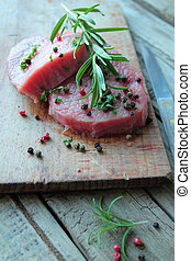 Raw beef steak with fresh rosemary on a wooden table