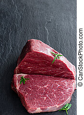 Raw beef steak with herbs on a dark stone slate
