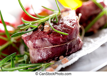 Raw beef steak with peppercorns and herbs