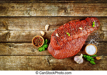 Raw beef steak with spices on a wooden background.