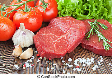 Raw beef steak with vegetables and spices on brown wooden background