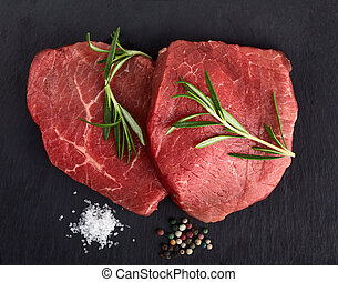 Raw beef steaks with rosemary