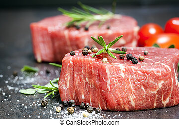 Raw Beef Steaks with spices and Rosemary over Slate - Raw...