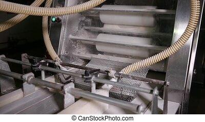 Raw bread moves along the conveyor