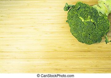 Raw broccoli on wooden cutting board