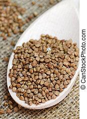 Raw buckwheat in a wooden spoon
