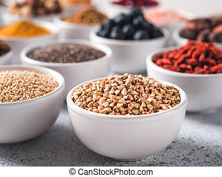Raw buckwheat in small bowl and other superfoods