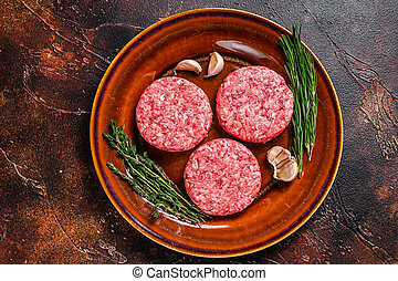 Raw burger meat cutlets with mince beef and herbs on a plate. Dark background. Top view