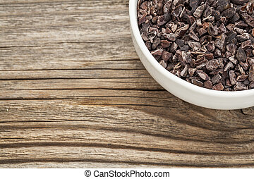 Raw cacao nibs in a small ceramic bowl against grained...