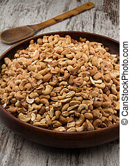 Raw cashews close-up in wooden bowl