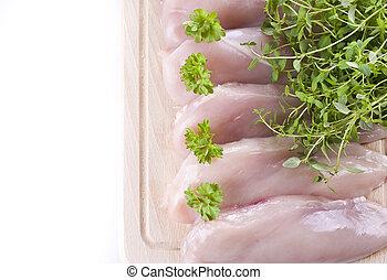 Raw chicken breasts on chopping board