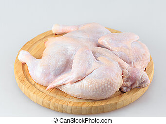 Raw chicken carcass on the cutting board isolated on white background.