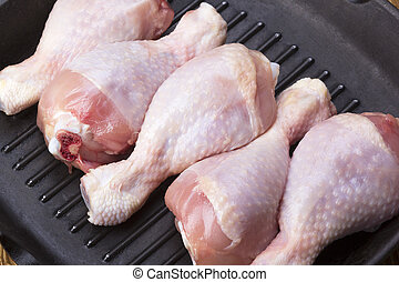 raw chicken drumstick in a pan