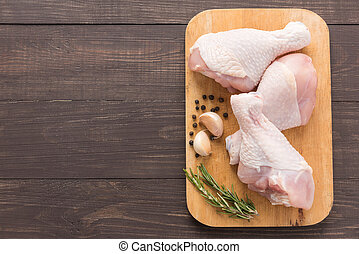Raw chicken drumsticks on cutting board on wooden background