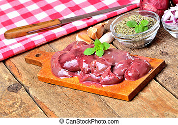 Raw chicken liver on a wooden cutting board, fresh garlic, dried marjoram, oregano, onion, knife and red checkered tablecloth in the background