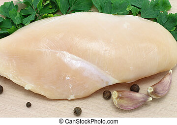 raw chicken on wooden board close-up
