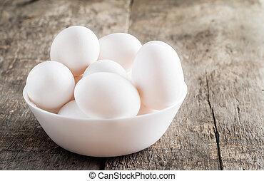raw chicken white eggs in white bowl on wooden background