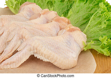 Raw chicken wings on wooden cutting board