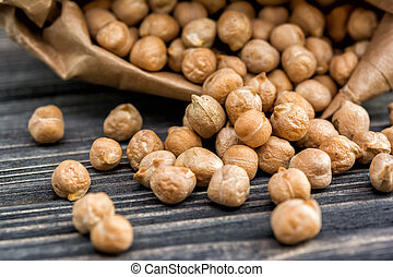 Raw chickpeas in paper bag on wooden background. Healthy ...
