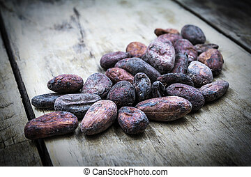 Raw cocoa beans on old wooden table