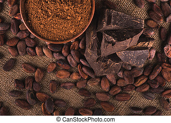 Raw cocoa beans, clay bowl with cocoa powder, black...