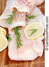 Raw Cod Fish Fillet with Lemon Slices and Rosemary closeup on Wooden background. Vertical View