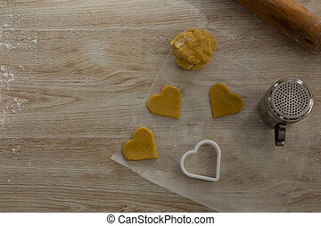 Raw cookie dough with heart shaped cookie cutter and flour shaker strainer