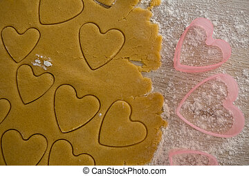 Raw cookie dough with heart shaped cookie cutter