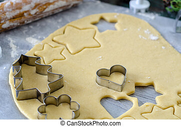 Raw cookies being cut with a star and heart cookie cutter