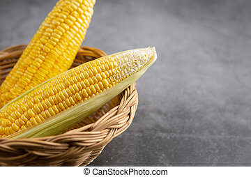 Raw corn in the basket on the black cement floor.