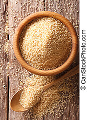 Raw Couscous in a wooden bowl and spoon on the table close-up. vertical top view